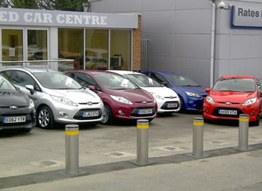 Rising bollards protecting cars at Ford dealership